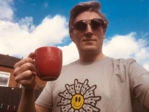 Simon Keegan holding a coffee and wearing a LeiMai and Lifeshare shirt