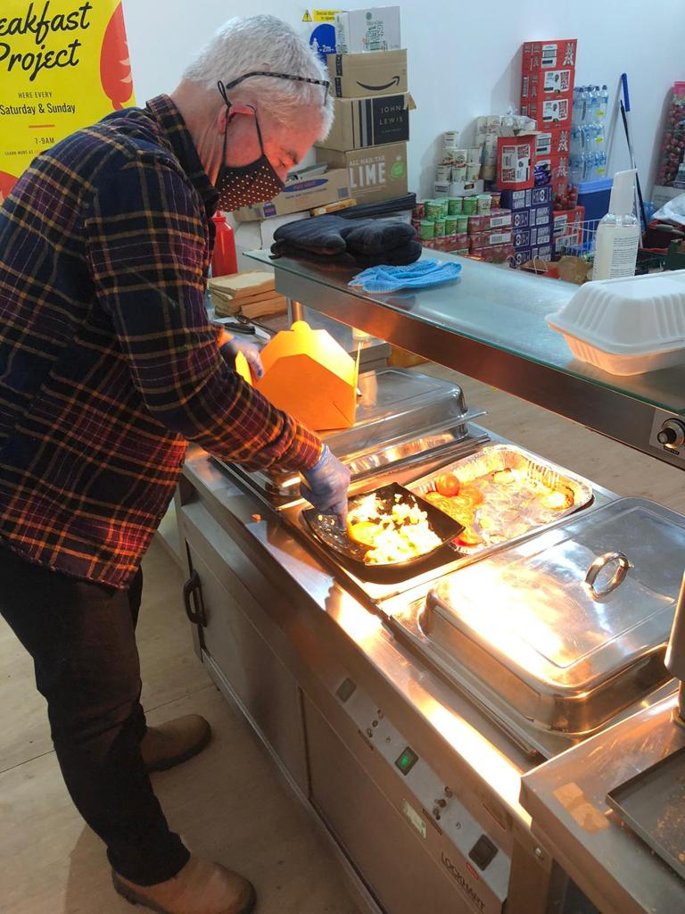 Lifeshare volunteer serving hot food during the Breakfast provision