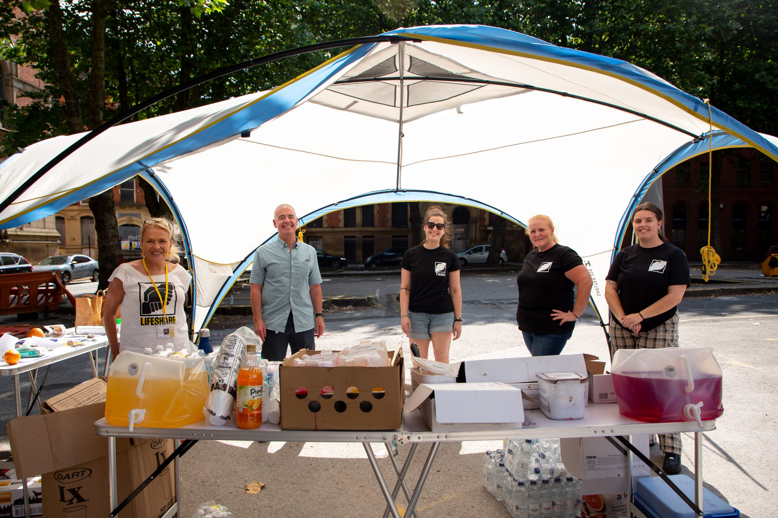 five lifeshare workers standing under a canopy
